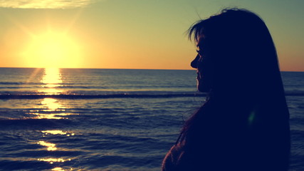 Retro style of woman watching sunset in front of the ocean