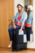 Woman with luggage near door