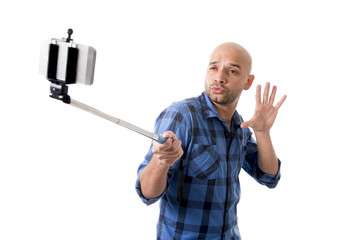 Hispanic man taking smartphone selfie picture holding stick