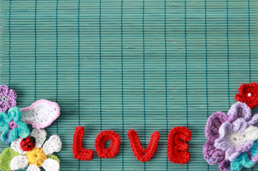 green background  with red crocheted superscription of love