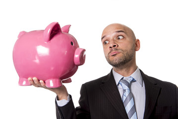 businessman holding huge pink piggy bank face to face