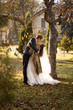 just married couple kissing passionately under tree at autumn pa