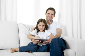 father on couch with young daughter using digital tablet pad