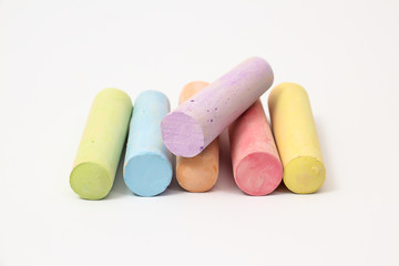 Pastel colored chalk sticks on a white background