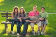 Five teenage boys and girls having fun in the park on sunny spri