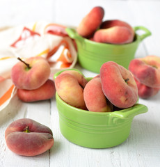 peach figs in a ceramic bowl on a white background