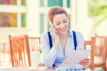professional woman talking on mobile phone reviewing documents