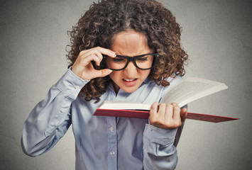 woman with glasses reading book having difficulties seeing text