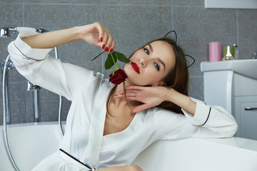 Sexy woman in bathroom in silk robe rose Valentine's day
