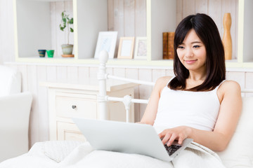 young asian woman using laptop in the bed room