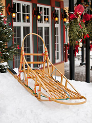 wooden dog sled on snow in village