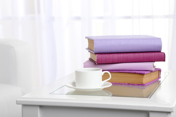 Purple books with cup near sofa