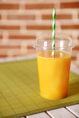 Orange juice in fast food closed cup with tube