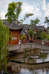 Wooden houes in Chinese style, picturesque bridge across the riv