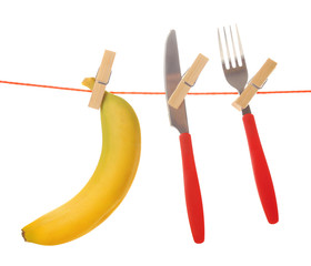 Fork, knife and banana hanging from clothesline isolated