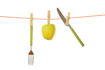 Fork, knife and apple hanging from clothesline isolated