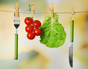 Fork, knife and vegetables  hanging from clothesline