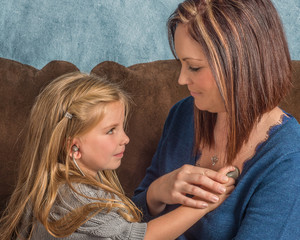 Beautiful little girl listening to her moms heart with a stethos