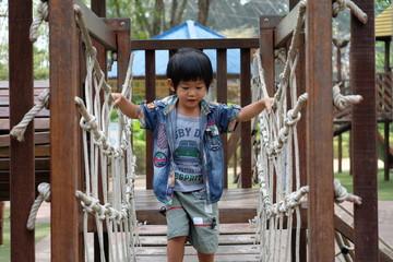 boy is crossing rope bridge in play ground