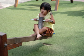 Pretty little asian girl Thai on outdoor seesaw in playground