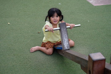 Pretty little asian girl on outdoor seesaw in playground
