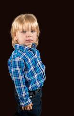 Solemn little boy against a dark background