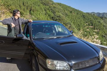 緑の山と車と男性