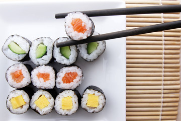 Chopsticks holding sushi from assorted sushi meal