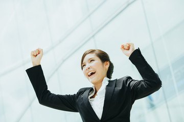 Young asian businesswoman rise her arms up as a winner gesture