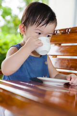 Little asian girl (thai) drinking from a cup