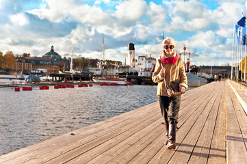 Cute stylish and trendy girl walking on pier in Stockholm.