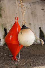 orange conical buoy and white spherical buoy hanging outside wat