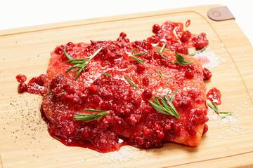 Salmon steak being marinated in salt with redberries