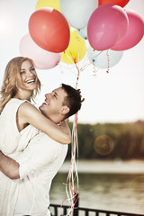 Young happy couple holding colorful ballons and embracing.