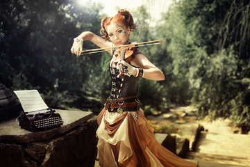 Attractive young woman playing on violin outdoors.