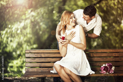 Man holding red box with ring making propose to his girlfriend