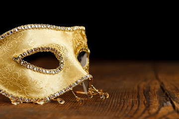 Golden mask on wooden table