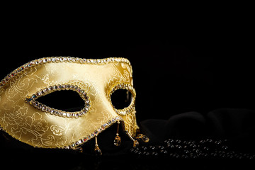 Golden mask near pearls on black