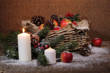 Apples and cones in a wattled basket, candles and a pine branch