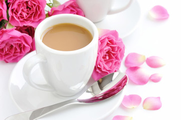 Cups of coffee and pink roses on white background