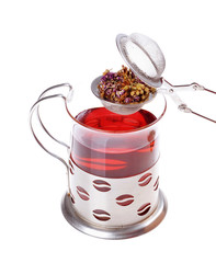 Glass cup of tea with a strainer on a white background