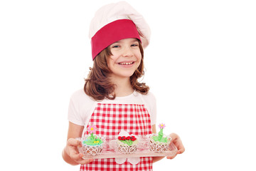 happy little girl cook with spring flower cupcakes