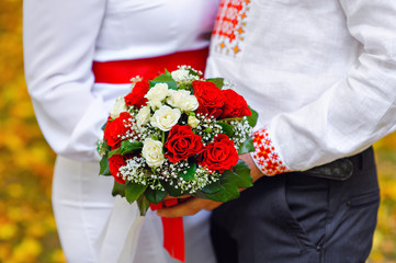 bride and groom holding a bouquet of red wedding