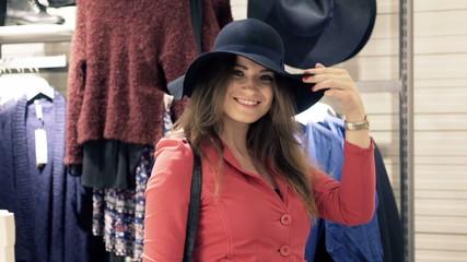 Portrait of pretty, happy woman trying stylish hat in shop