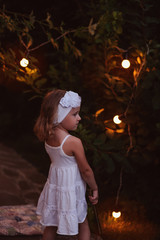 child girl with book in summer evening garden with lights