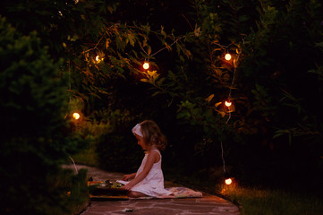 child girl reading book in summer evening garden with lights