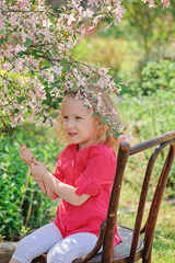 adorable child girl under blooming cherry tree in spring garden