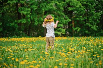 child girl in wreath walks on spring dandelion field