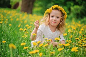 adorable child girl in wreath portrait on spring dandelion field