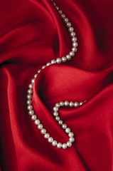 White pearls on a red silk